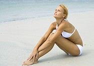 Woman in bikini sitting on beach, hugging knees, full length