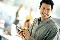 Man using electronic organizer, smiling