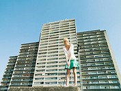 Woman playing golf by apartment block