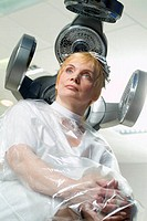 mature woman sitting in hair salon under hair dryer