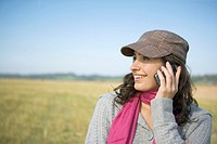 smiling woman talking on cellular phone outdoors