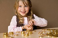 smiling young girl playing with gold coins