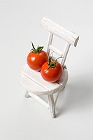 Two cherry tomatoes on a chair