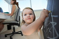 Businesswoman With Daughter Using Blackboard