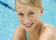 Young woman smiling, portrait, pool in background
