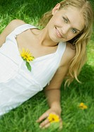 Woman lying in grass with flower in dress, smiling at camera