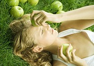 Woman lying in grass, holding apple to forehead