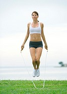 Young woman jumping rope, outdoors