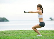 Young woman working out with weights, outdoors