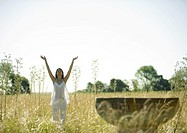 Woman standing in sun salutation pose, in field