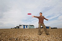 Low angle view of a young man throwing a plastic disc on the beach