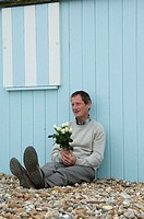 Mature man leaning against a beach hut and holding a bunch of flowers
