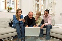 Young couple sitting on a couch with their parents and using a laptop