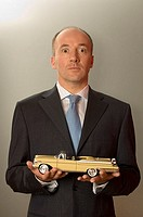 Portrait of a businessman holding a toy car
