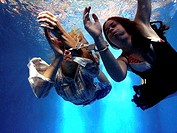 Close-up of two teenage girls handcuffed underwater