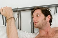 Close-up of a young man´s hand handcuffed to the bedpost