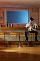 Man sitting at bar on stool from behind