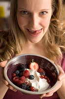 Close up of woman offering crème fraiche and fruit