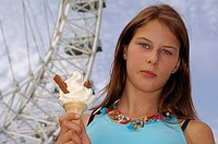 Portrait of a young woman holding an ice-cream cone with a ferris wheel in the background