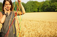 Young woman standing in a field holding power cables and talking on a mobile phone