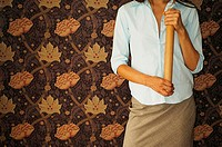 Mid section view of a businesswoman holding a bamboo stick