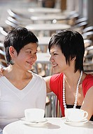 Mother and adult daughter in cafe, smiling at each other