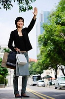 Woman in city, holding shopping bags, flagging cab