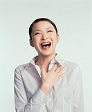 Young woman laughing, hand on chest