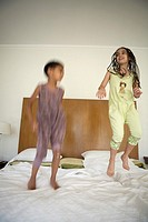 Siblings jumping on bed