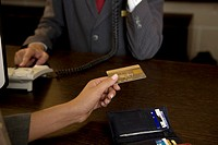 Businesswoman handing over gold credit card