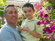 Father holding son in garden centre