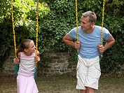 Father and daughter playing on swings