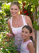 Mother and daughter standing near plants