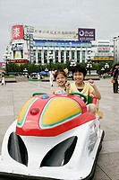 Boy and girl sitting in a toy car and smiling