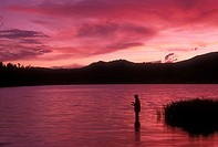 Silhouette of a person fishing in a lake