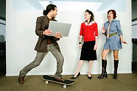 Businessman holding a laptop and riding a skateboard past two businesswomen