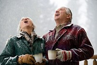 Senior couple holding coffee cups and looking up with their mouths open