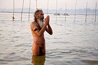A nagababa sadhu praying alone in the sacred Ganges during the Ardh kumbh Mela 2007 in Prayag