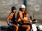 A man woman and child riding a motor scooter