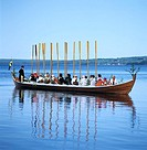 People sitting on a boat with oars