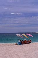 People sitting on the beach with umbrellas
