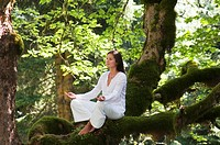 Young woman meditating, sitting on tree