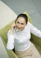 Businesswoman sitting in armchair using cellphone