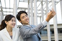 Businessman standing next to female colleague, taking photo with cell phone