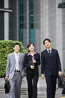Three young executives walking side by side