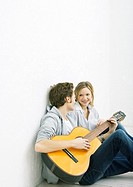 Young man and woman sitting on ground, man playing guitar