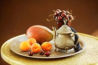 Teapot with fruits on tray, standing on table