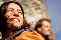 Couple resting in mountains, focus on woman