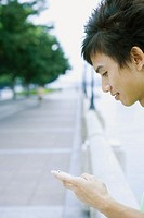 Young man using cell phone, cropped view of head and hand