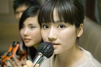 Young woman holding microphone in karaoke bar, close-up, friends in background